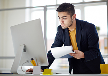 worker standing up in front of laptop