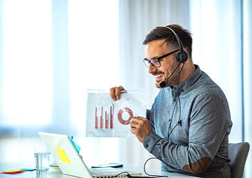 employee wearing a headset and showing charts on the computer